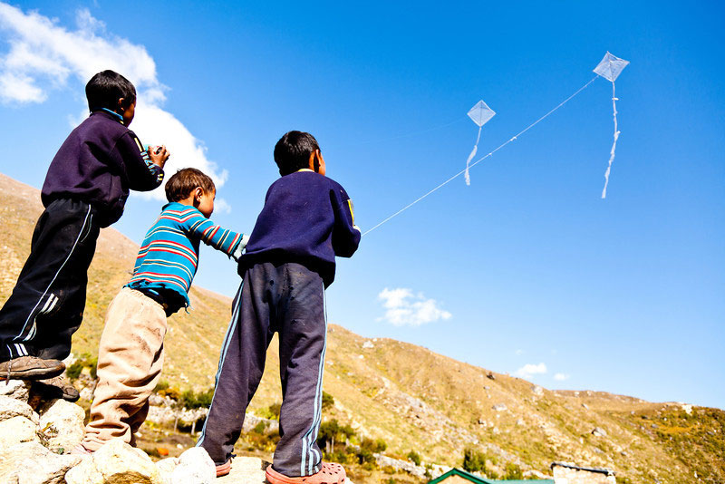 Child on rural area enjoying their kites on open sky